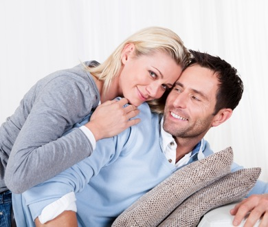 Happy attractive young man and woman smiling and cuddling as he relaxes on the sofa